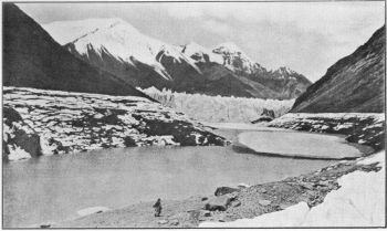 The Kyagar Glacier Dam across the Shaksgam Valley in 1926. The upper level of the ice-blocks on the hillsides indicates the winter level of the frozen lake. The lowered water level shows that percolation through the dam has exceeded drainage into the lake since winter. (Photo. Kenneth Mason.)