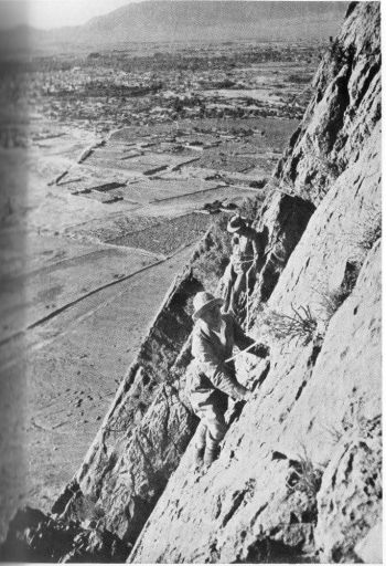 Rock climbing on the practice slabs near Volunteer Point, Quetta. The mins of Quetta city in the middle distance with the cantonments beyond