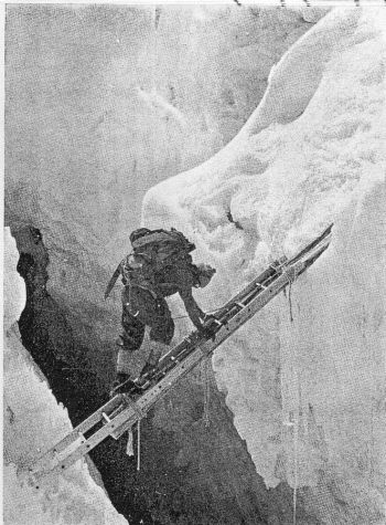 Sherpas crossing a crevasse on legs and section of a light bridge