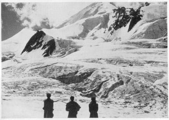 PORTERS ON THE WAY TO CAMP BELOW FALAK SER, WHICH IS SEEN IN THE BACKGROUND